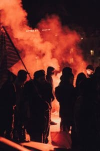 Rioters at night with smoke in background.