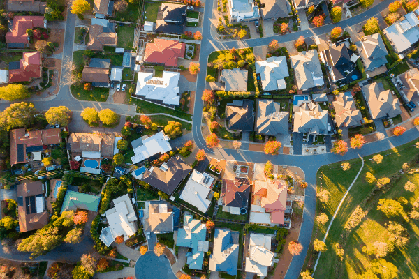 A view of the suburbs with a few dozen houses, looking down at the roof tops.
