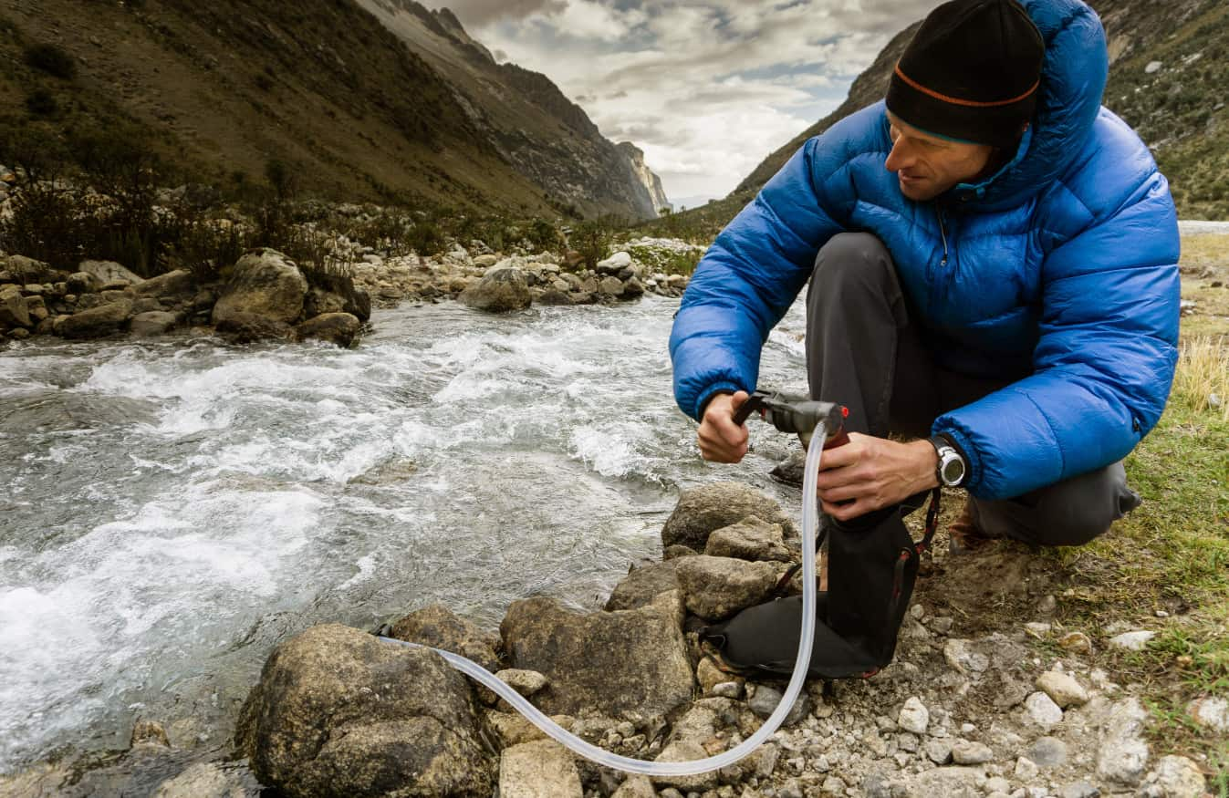 traveler collecting water from stream