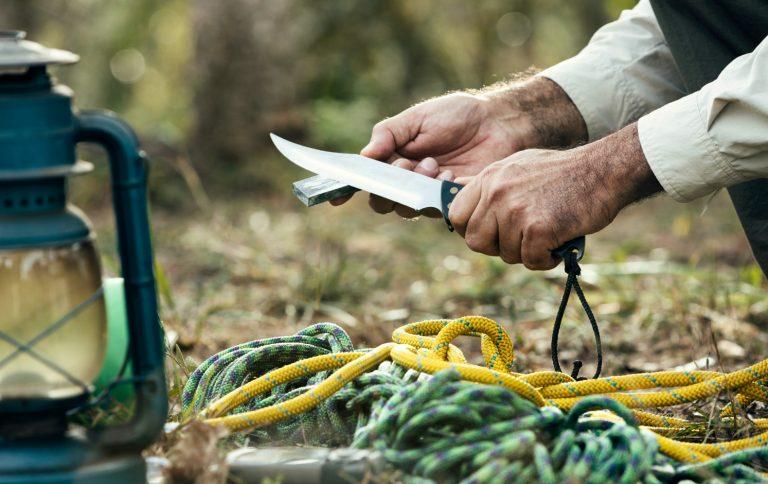man sharpening knife outdoor